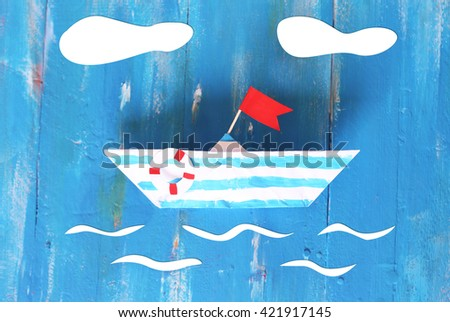 Photo of cute origami paper boat on wooden backgrond - stock photo