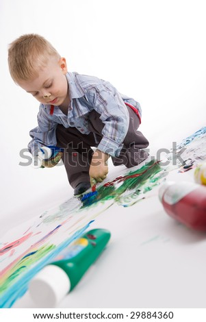 Photo of cute preschooler painting something with colorful gouache - stock photo