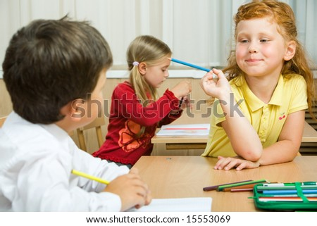 Photo of cute schoolgirl with blue pencil in hand looking at her classmate during lesson - stock photo