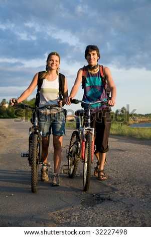 Photo of cyclists with bikes walking down country road during summer vacations - stock photo