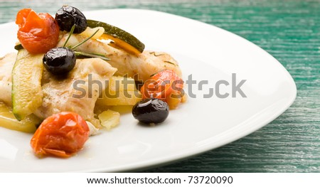 photo of delicious baked cod with olives and tomatoes - stock photo
