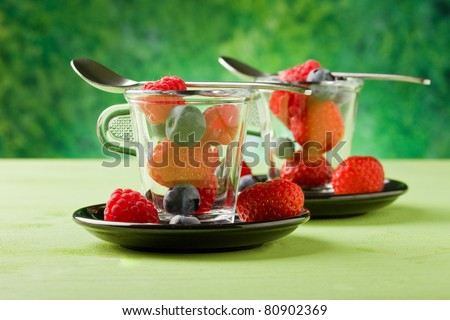photo of delicious berries inside a glass cup with green background
