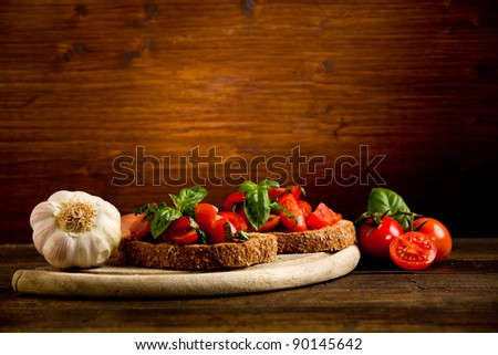 photo of delicious bruschetta appetizer with fresh cutted tomatoes and basil - stock photo