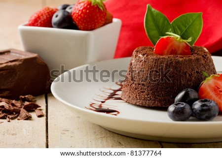 photo of delicious chocolate dessert with berries on wooden table - stock photo