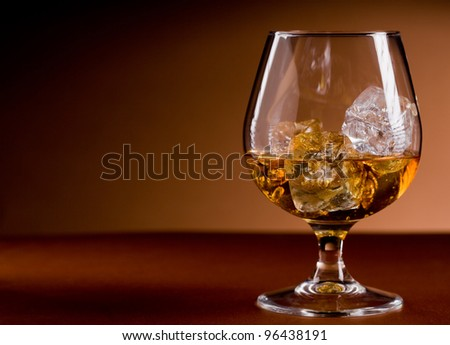 photo of delicious glass of cognac whiskey with ice cubes on brown background - stock photo