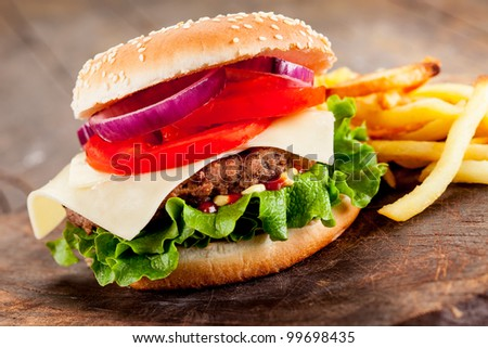 photo of delicious hamburger with fries on wooden table - stock photo