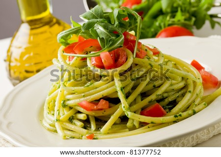 photo of delicious pasta with arugula pesto and cherry tomatoes - stock photo