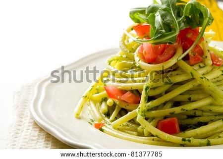 photo of delicious pasta with arugula pesto and cherry tomatoes - stock photo