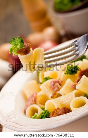 photo of delicious pasta with sausage and broccoli on wooden table - stock photo