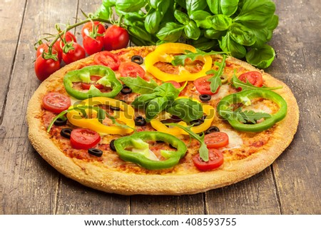 Photo of delicious pizza with paprika over wooden table