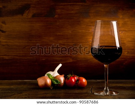photo of delicious red wine goblet with fresh ingredients on wooden table - stock photo