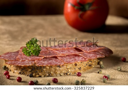 Photo of delicious salami sandwich with peppercorns and parsley