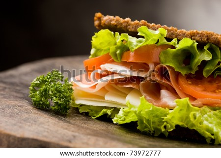 photo of delicious sandwich with smoked bacon and cheese on wooden table - stock photo