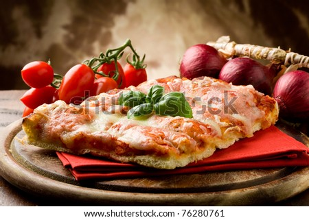 photo of delicious slice of pizza with basil leaf on it - stock photo