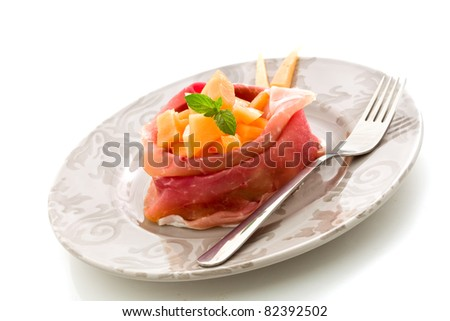 photo of delicious sliced bacon with melon inside on white isolated background