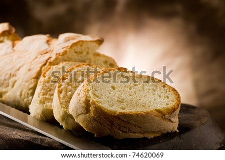 photo of delicious sliced bread on wooden table with knife - stock photo