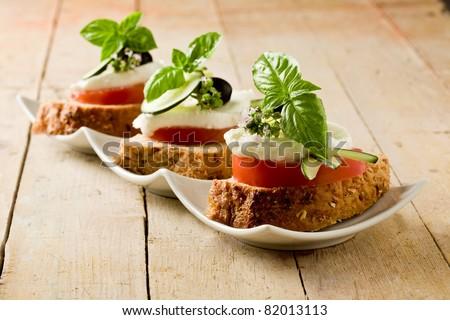 photo of delicious sliced cereal bread with tomato mozzarella - stock photo