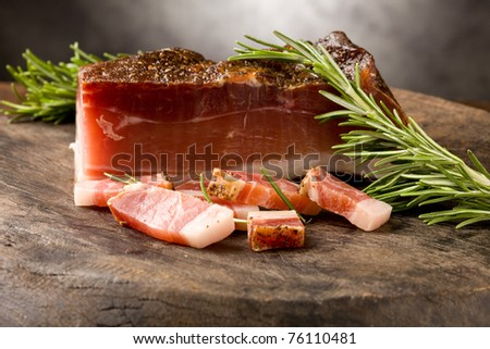 photo of delicious smoked ham on wooden table with rosemary - stock photo