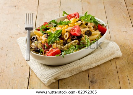 photo of delicious tasty pasta salad on wooden table with fresh vegetables - stock photo