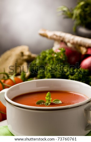 photo of delicious tomato soup with vegetables on wooden table - stock photo