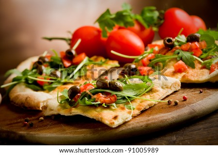 photo of delicious vegetarian pizza with arugula on wooden table - stock photo
