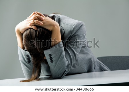 Photo of depressed female sitting at workplace and grieving - stock photo