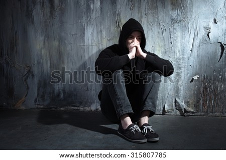 Photo of desperate young drug addict wearing hood and sitting alone in dark - stock photo