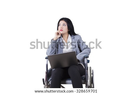 Photo of disabled businesswoman daydreaming on the wheelchair while holding laptop computer, isolated on white - stock photo