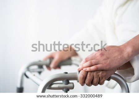 Photo of disabled old person with walking aid - stock photo