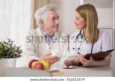 Photo of doctor and ill elderly man with medicines - stock photo