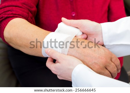 Photo of doctor bandaging the elderly woman wrist - stock photo