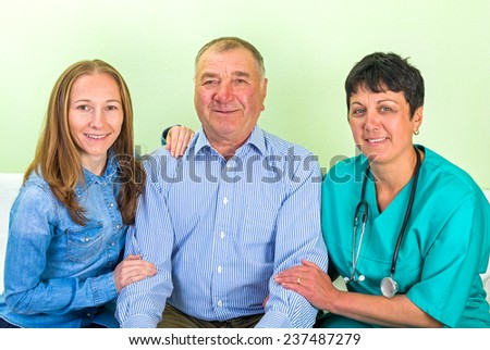 Photo of elderly man with his daughter and doctor - stock photo