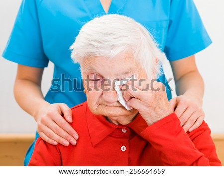 Photo of elderly woman supported by young carer - stock photo