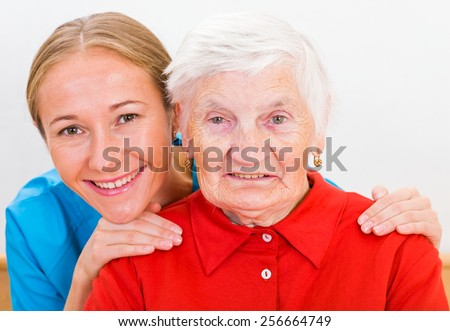 Photo of elderly woman supported by young doctor - stock photo