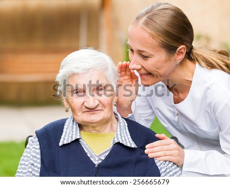Photo of elderly woman with young carer - stock photo