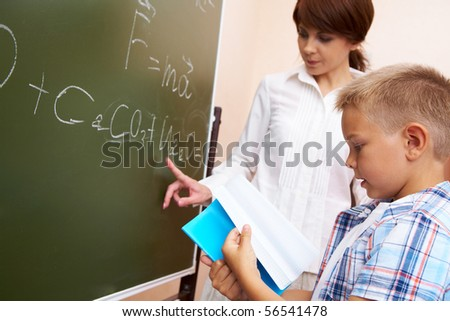 Photo of elementary student holding copybook with his teacher pointing at blackboard - stock photo