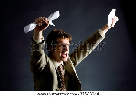 Photo of emotional businessman with papers raising his arms - stock photo