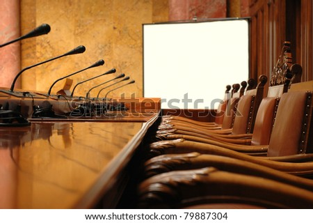 Photo of empty conference room with microphones and blank billboard - stock photo