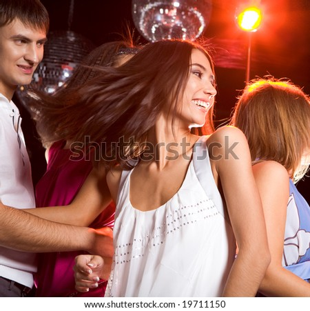 Photo of energetic girl dancing in the night club with her boyfriend looking at her