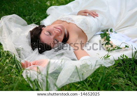 Photo of enjoying woman with closed eyes lying on the grass after marriage