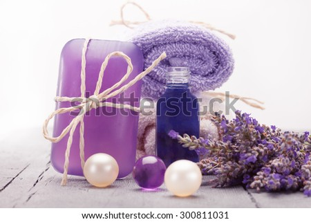 Photo of essential oil  and soap with lavender over wooden table - stock photo
