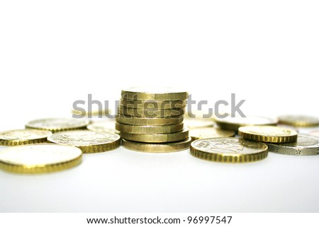 Photo of euro coins with some stacked on each other on white and grey background