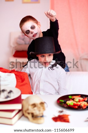 Photo of evil boy scaring his brother with spider on Halloween - stock photo