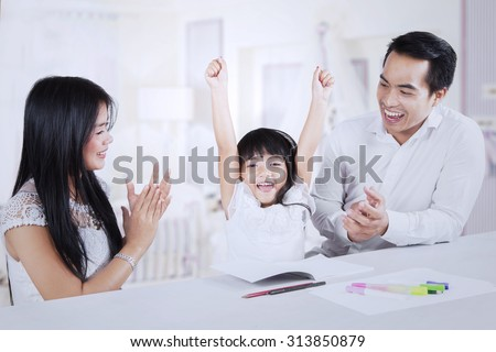 Photo of excited little girl finishing her homework and get applause from her parents at home - stock photo