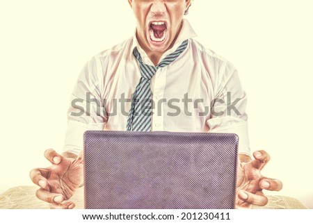 photo of exhausted, angry and overworked half face business man  with laptop in front him on office desk at his work, vintage high contrast style