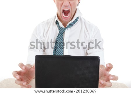 photo of exhausted, angry and overworked half face business man with laptop in front of him on office desk at his work - stock photo
