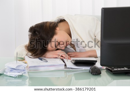Photo Of Exhausted Young Businesswoman Sleeping On Desk - stock photo