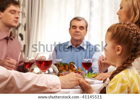 Photo of family members praying at festive table while holding each other by hands