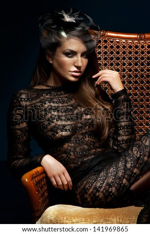 Photo of fashionable brunette beautiful woman posing in black hat, looking at camera. Elegant girl sitting on chair. - stock photo