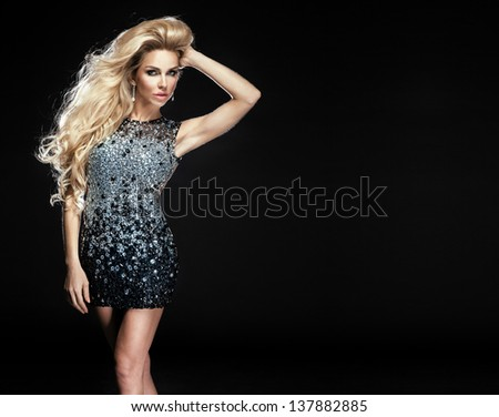 Photo of fashionable young blonde woman wearing elegant diamond dress. Long healthy curly hair. A lot of empty space. - stock photo